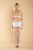 Back view of a semi nude woman in white lingerie