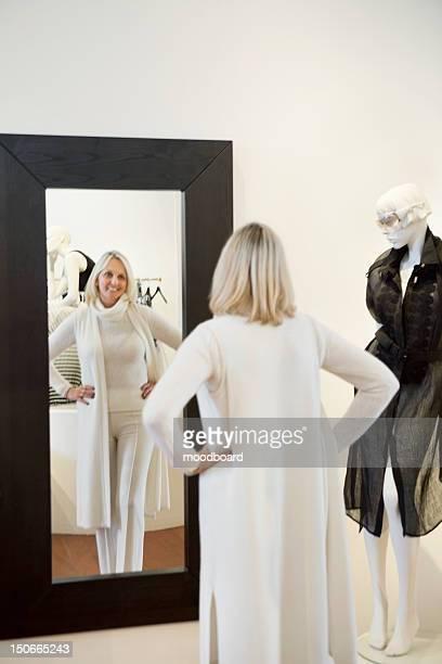 Back view of a senior woman standing with hands on hips in front of mirror looking at herself