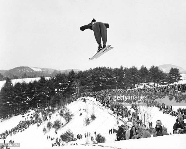 A back view of a skier going off the ski jump at the annual Winter Carnival of the Dartmouth Outing Club Hanover New Hampshire circa 1955