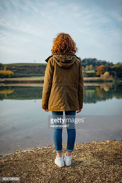 Back view of a teen girl at the lakeshore