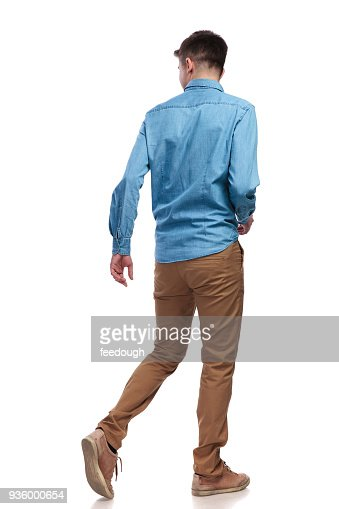 back view of a walking casual man looking to side : Stock Photo