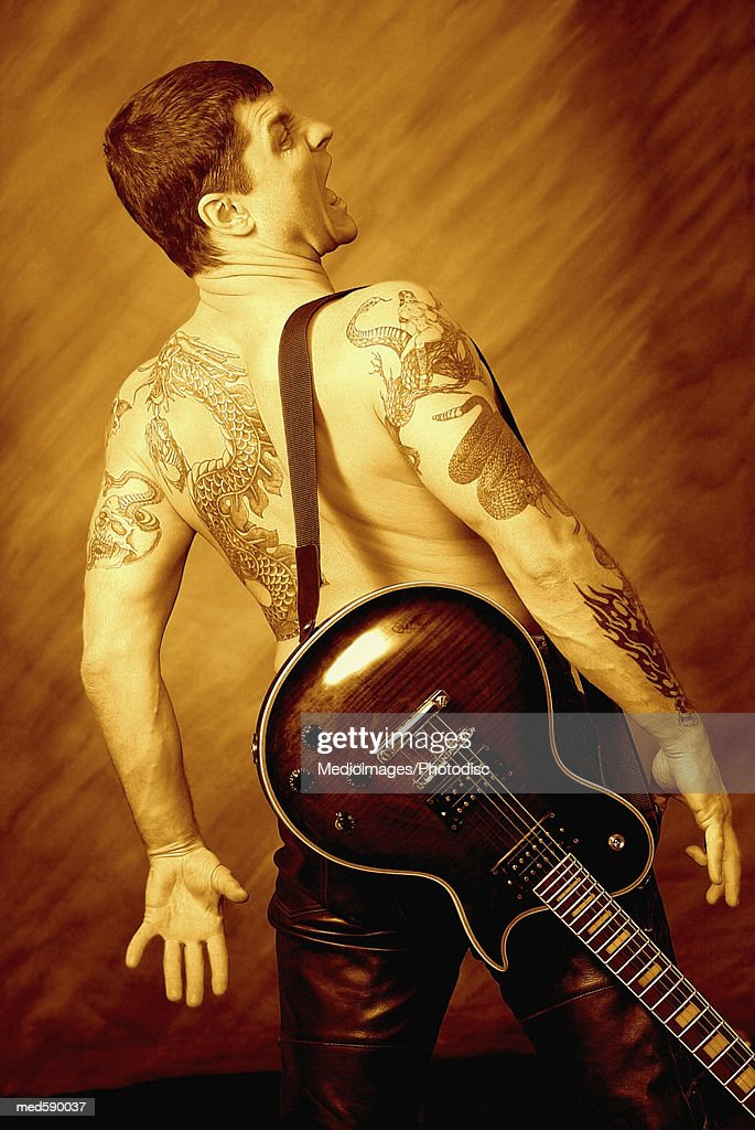 Back view of bare-chested, tattooed man with guitar : Stock Photo