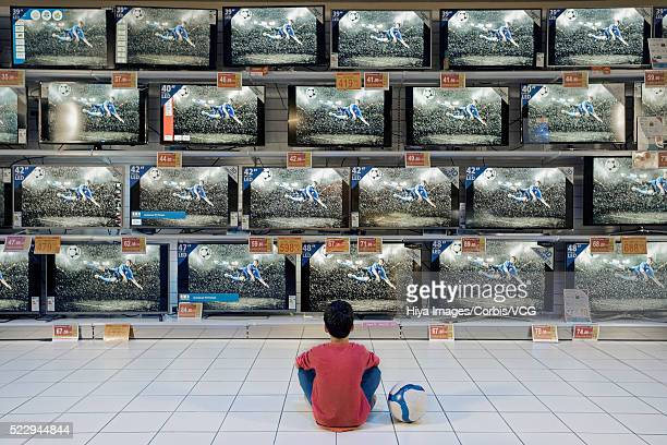 Back view of boy watching soccer in electronics store