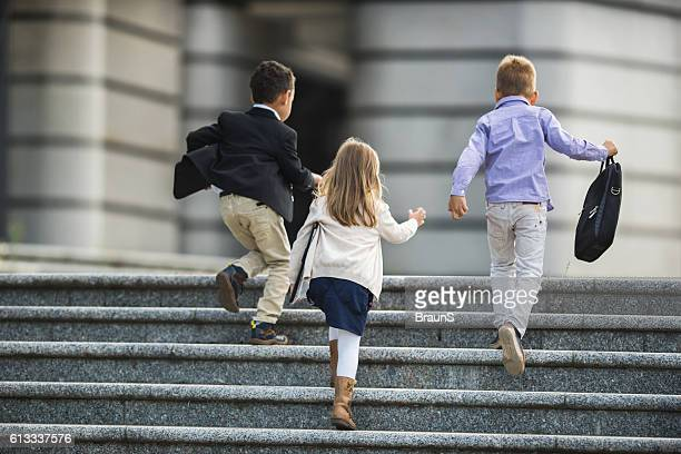 Back view of business kids running up the stairs.