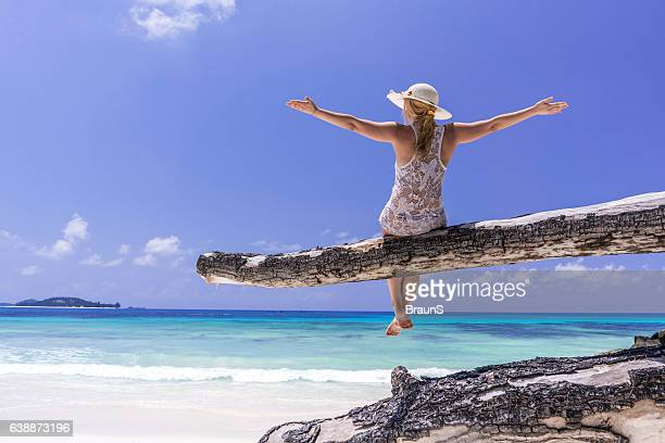 Back view of carefree woman on tree trunk at beach.
