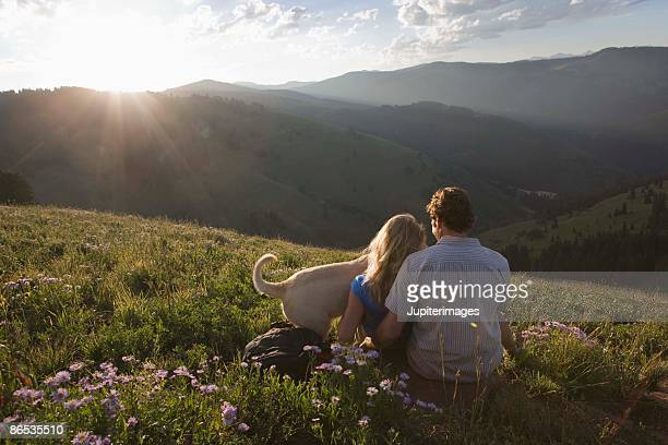 Back view of couple with dog on mountainside