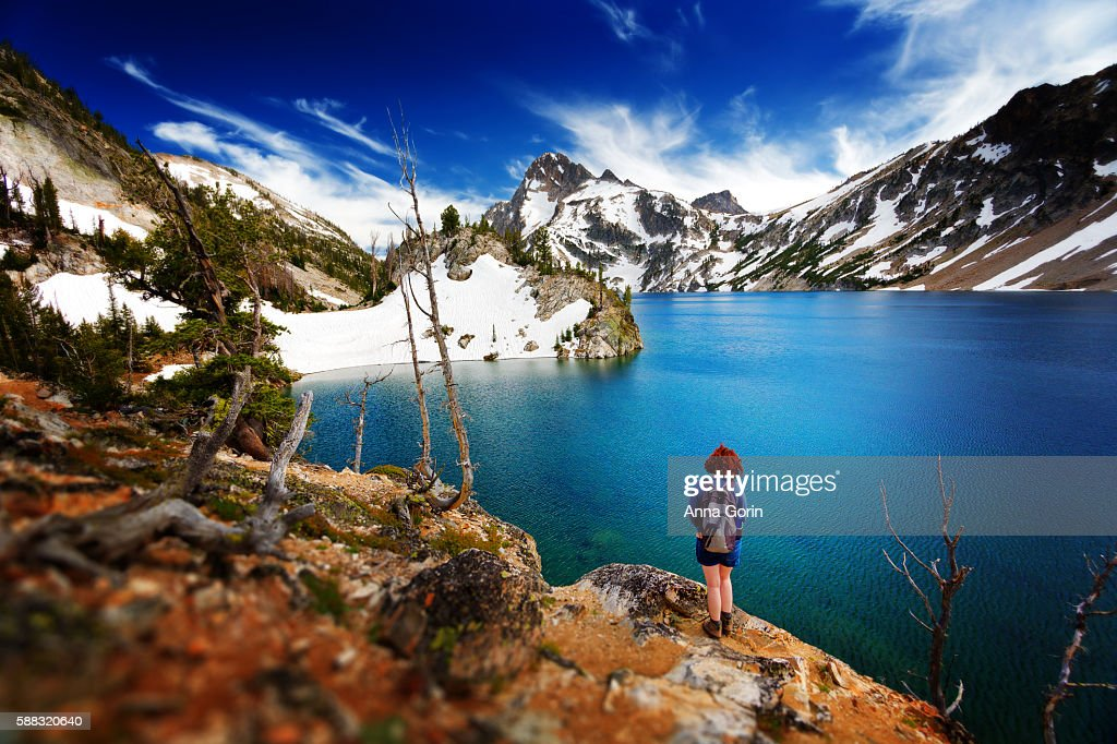 Back view of female hiker standing by shores of Sawtooth Lake in Stanley, Idaho