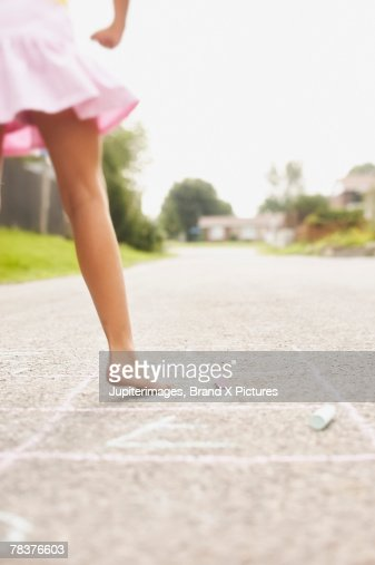 Back view of girl playing hopscotch : Stock Photo
