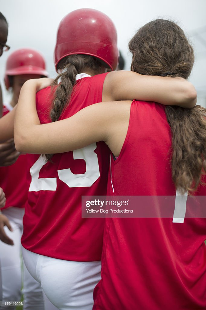Back View of Girls Hugging at Softball Game : Stock Photo