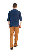 Back view of going  handsome man in jeans and a shirt.  walking young guy . Rear view people collection.  backside view of person.  Isolated over white background.  man in brown pants, shirt sleeves r