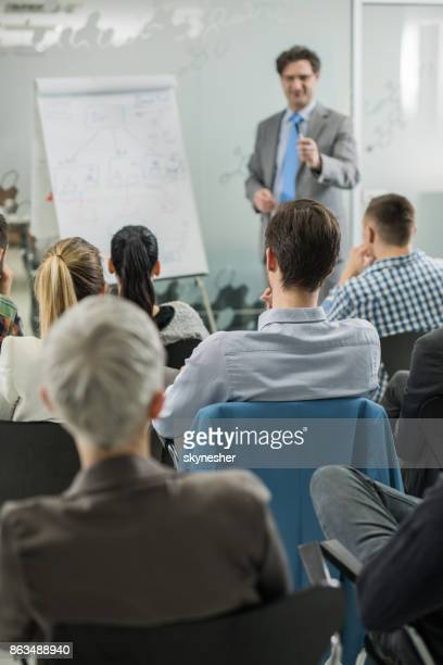 Back view of group of business people attending a seminar.