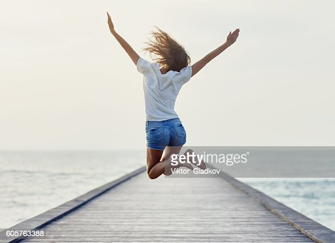 Back view of jumping girl on the pier : Stock Photo