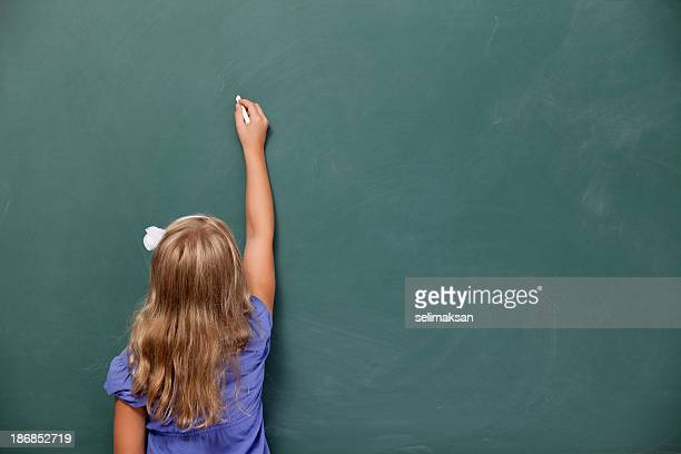 Back view Of Little Girl Writing On Blank Blackboard