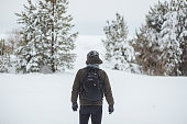 Back view of man hiker with backpack looking to frozen sea and to trees covered snow.
