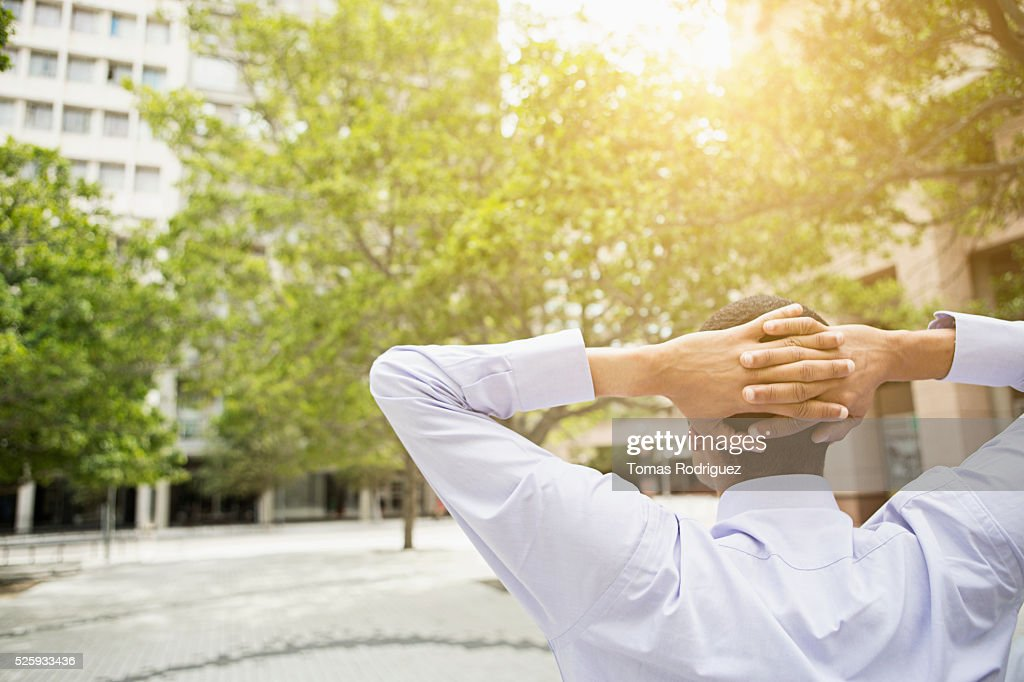 Back view of man relaxing, hands behind head : Stock Photo