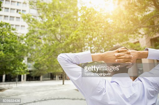 Back view of man relaxing, hands behind head : Stockfoto