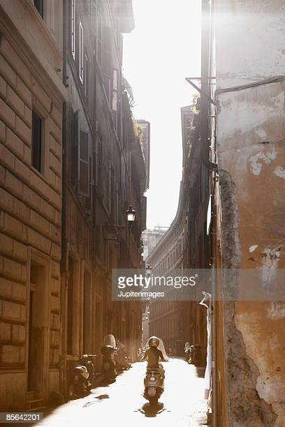 Back view of man riding scooter in alley