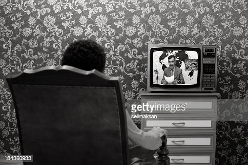 Back View Of Man Sitting And Watching News On Television