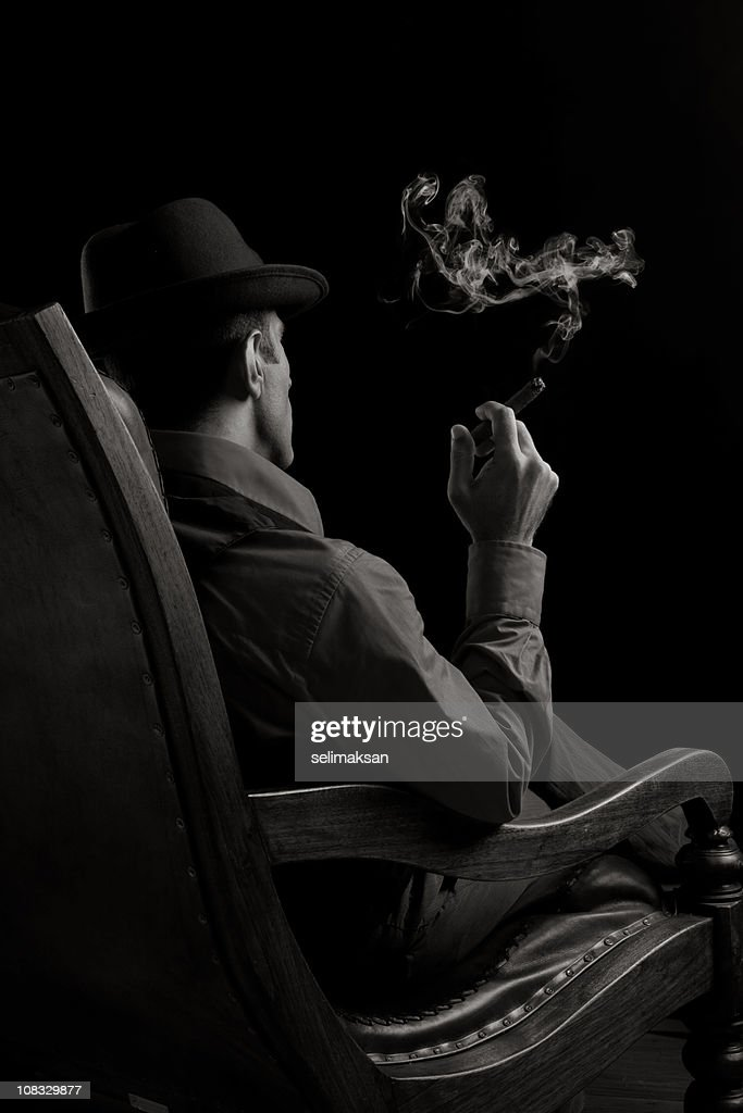 Man sitting on armchair and smoking cigar