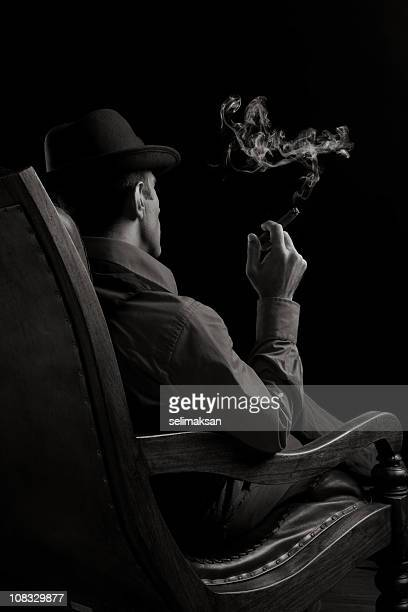 Back View Of Man Sitting On Armchair And Smoking Cigar