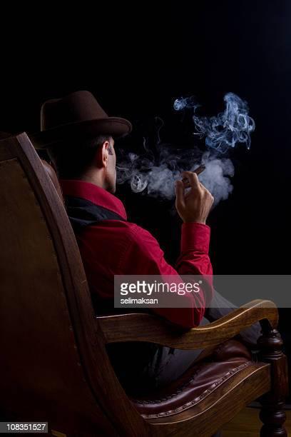 Vue arrière de l'homme assis sur un fauteuil et les fumeurs de cigare