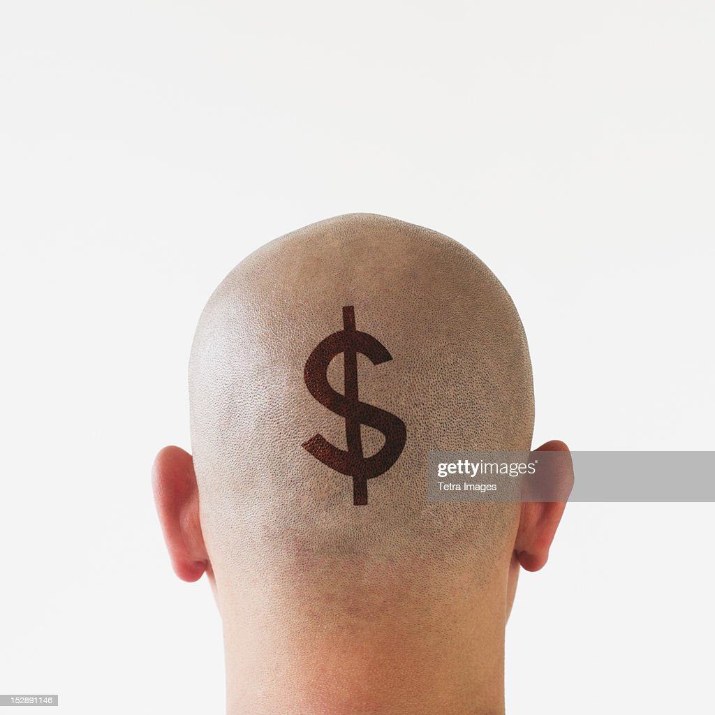 Back view of man with dollar sign on shaved head : Stock Photo