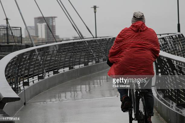 Back view of man with raincoat cycling