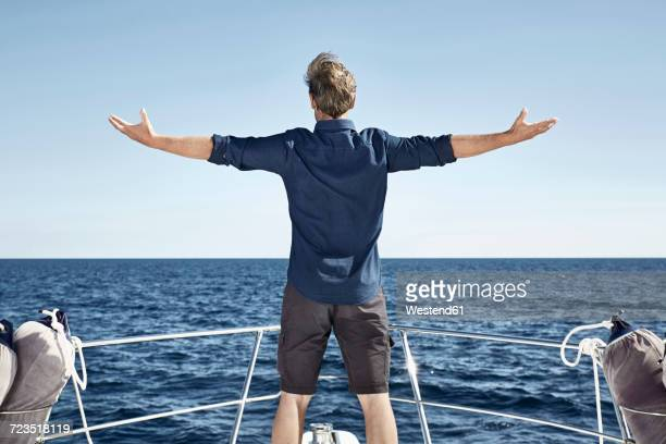 Back view of mature man standing on his motor yacht with arms outstretched