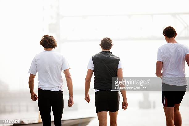 Back view of men walking to boat