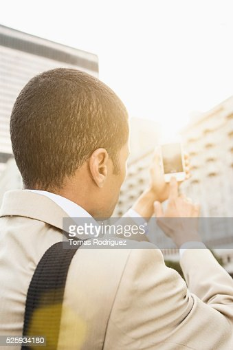 Back view of mid adult man photographing with cell phone : Stock Photo
