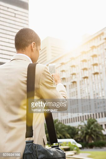 Back view of mid adult man using cell phone : Foto stock