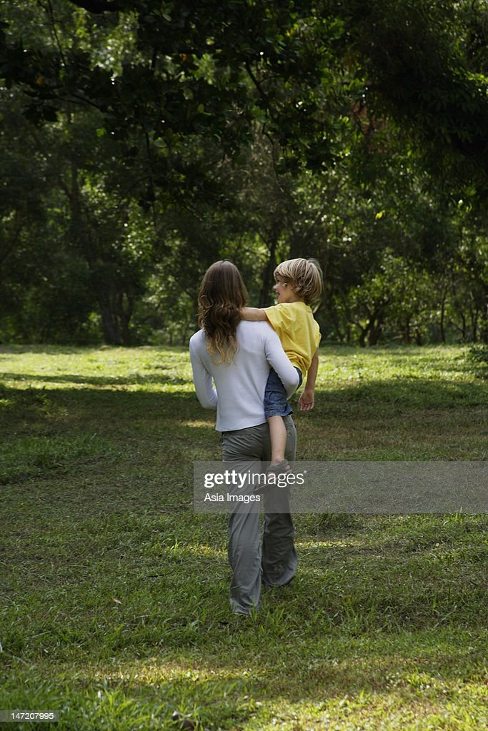 Back view of mother carrying her son while they walk in a park. : Stock Photo