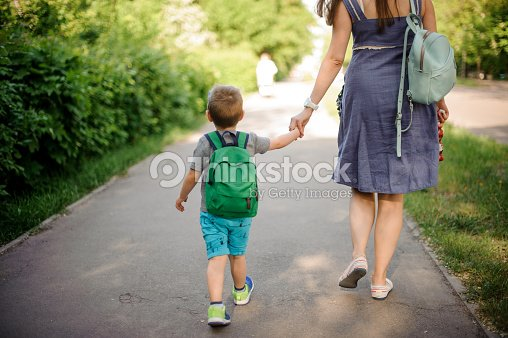 Back view of mother walking down the street with a little son with a backpack on sunny day : Stock Photo