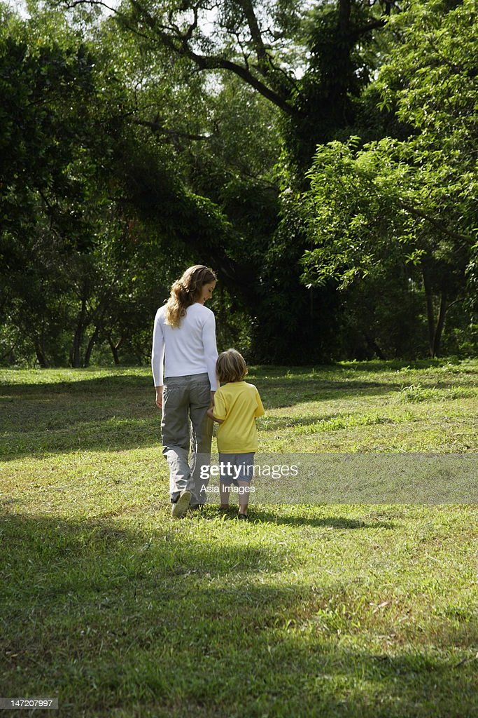 Back view of mother walking with her son in a park. : Stock Photo