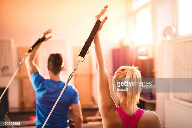 Back view of Pilates reformers exercising in a health club.