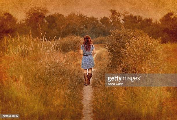 Back view of redhead walking down path, textured