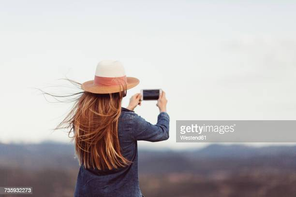 Back view of redheaded woman taking picture with smartphone in nature