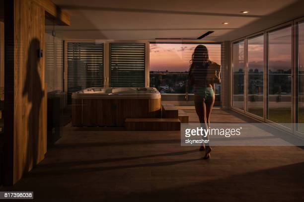 Back view of sensual woman going towards jacuzzi in a penthouse.