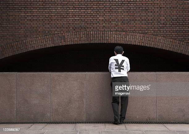 Back view of standing man wearing yen sign