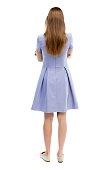 back view of standing young beautiful  woman.  girl  watching. Rear view people collection.  backside view of person.  Isolated over white background. The girl in the blue dress standing with her hand