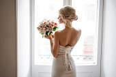 Back view of the elegant blonde bride dressed in a white dress holding a wedding bouquet on the background of window. Wedding concept