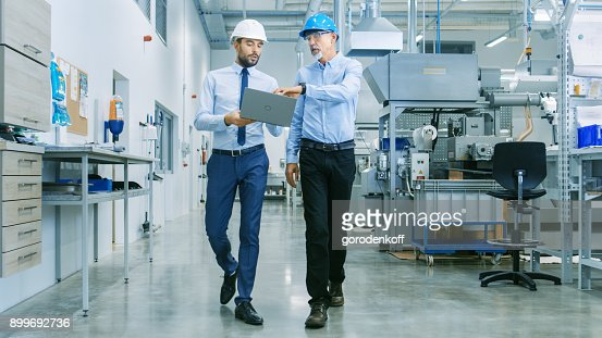 Back View of the Head of the Project Holds Laptop and Discussing Product Details with Chief Engineer while They Walk Through Modern Factory. : Foto stock