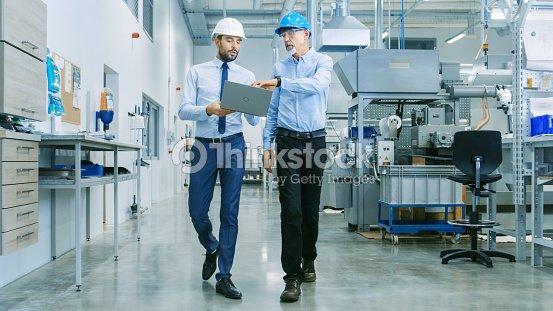 プロジェクトを保持しているノート パソコン彼ら歩くを介して近代的な工場中チーフ エンジニアと製品の詳細を議論するの頭の背面します。 : ストックフォト