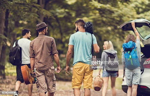 Back view of two men going on camping with friends.