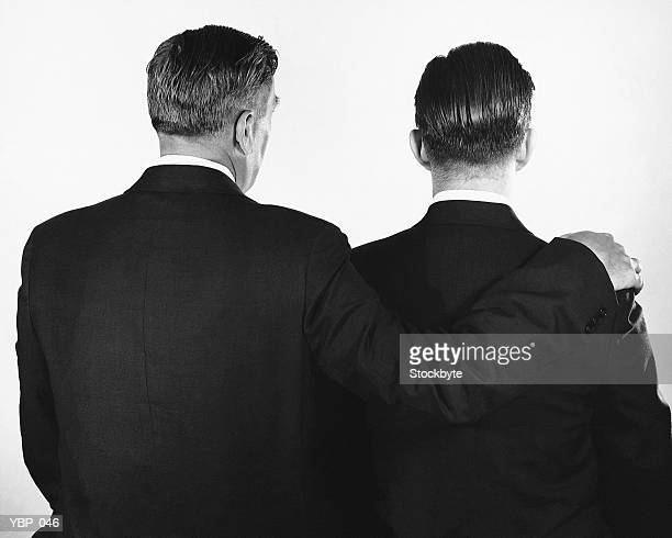 Back view of two men, one with arm around other