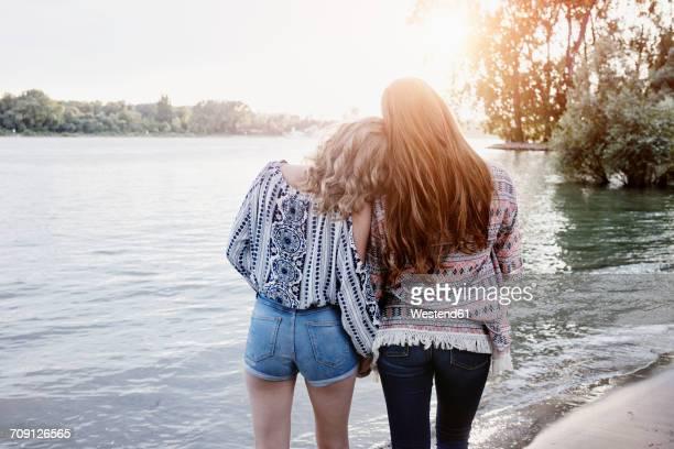 Back view of two teenage girls watching sunset at riverside