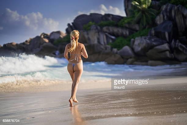 Back view of woman in bikini running on the beach.