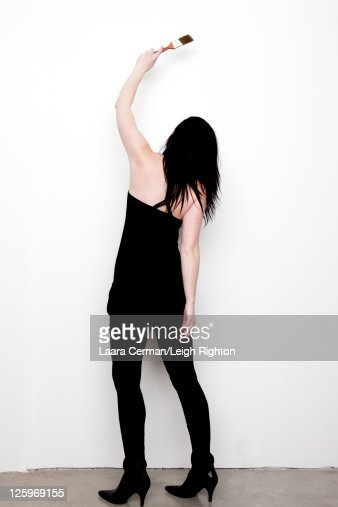 Back view of woman (28 years old) in black dress painting wall : Stock Photo
