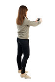 Back view of woman photographing.   girl photographer in jeans. Rear view people collection.  backside view of person.  Isolated over white background. A girl in a gray jacket photographs holding the