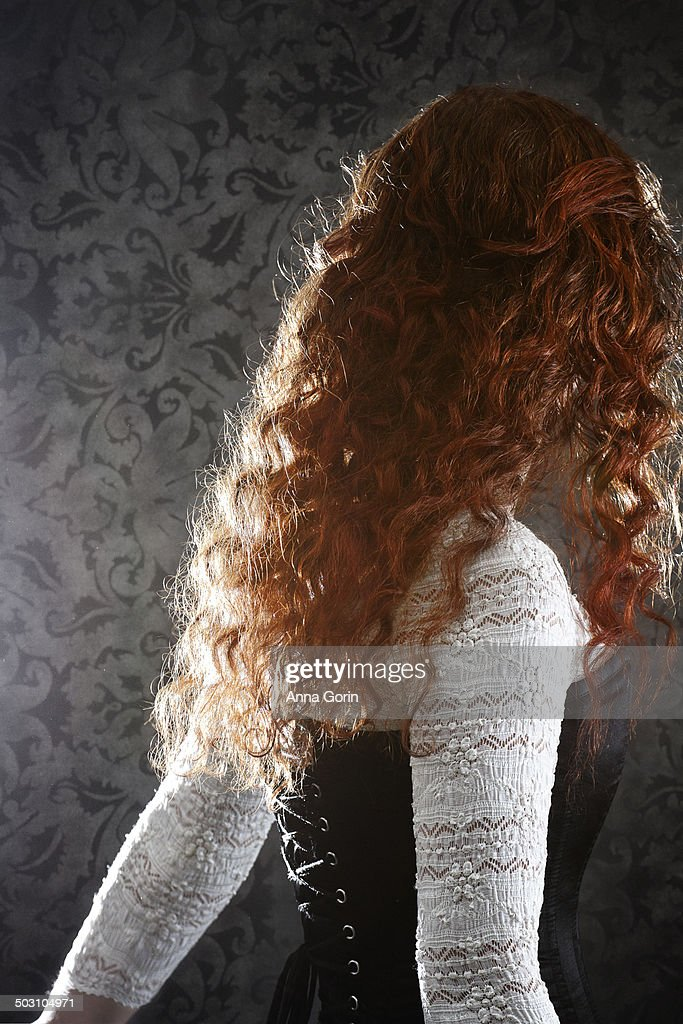 Back view of woman with curly red hair in corset
